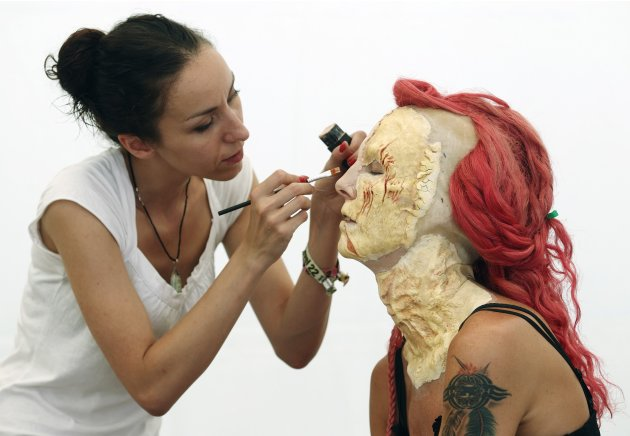 An artist paints a model during the annual World Bodypainting Festival in Poertschach