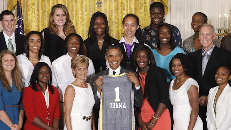 President Barack Obama holds up a team jersey as he stands with head coach Kim Mulkey, third left, at a ceremony honoring the 2012 NCAA Women's basketball champions Baylor University Bears in the East Room at the White House in Washington, Wednesday, July 18, 2012. (AP Photo/Charles Dharapak)