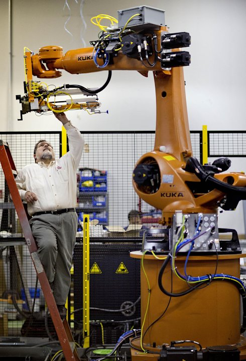 In this Jan. 15, 2013, photo, Rosser Pryor, Co-owner and President of Factory Automation Systems, examines a new high-performance industrial robot at the company's Atlanta facility. Pryor, who cut 40