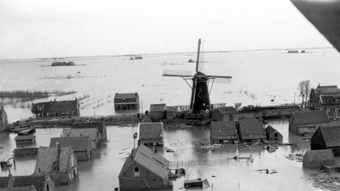 """FILE - This February 1953 file photo shows an aerial view of a windmill pump elevated above the floodwaters in the coastal village of Oude Tonge in The Netherlands. It took the collapse of dikes, drowning deaths of more than 1,800 people, and evacuation of another 100,000 in 1953 for the Dutch to say """"Never again!"""" They have since constructed the world's sturdiest battery of dikes, dams and barriers. No disaster on that scale has happened since. (AP Photo/File)"""