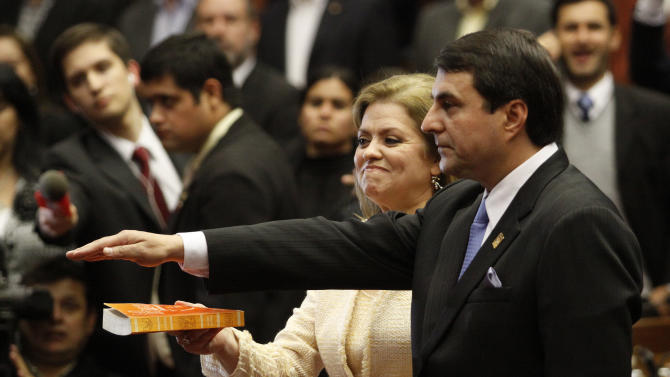 Paraguay's Vice President Federico Franco holds his hand over a bible held by his wife, lawmaker Emila Alfaro, as he is sworn-in as the nation's new president at Congress in Asuncion, Paraguay, Friday, June 22, 2012. Franco was promptly sworn in as president after Paraguay's Senate voted to remove President Fernando Lugo from office in an impeachment trial. (AP Photo/Cesar Olmedo)