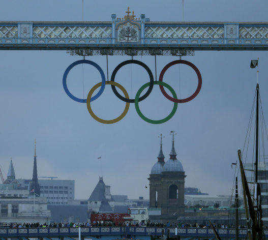 A crowd gathers beneath the Olympic Rings on the Tower Bridge in London, as they wait for the Olympic Torch to arrive at the Tower of London, Friday, July 20, 2012. The Olympic Torch arrived in London after it was carried around England in a relay of torchbearers to make its way to the London 2012 Olympic Games opening ceremony on July 27, 2012. (AP Photo/Charlie Riedel)
