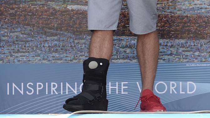 Former Olympic and world swimming champion Michael Phelps of the US wears a ankle cast as he attends the unveiling of a mosaic installed in his honour at the FINA Swimming World Championships in Barcelona, Spain, Sunday, July 28, 2013 .(AP Photo/Manu Fernandez)