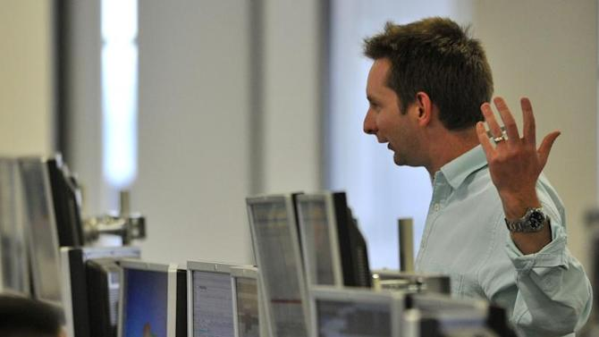 A dealer reacts on the trading floor of IG Index in the City of London