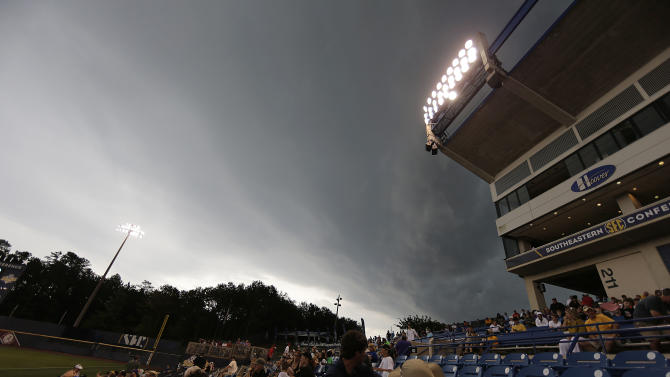 Fans watch clouds move over the stadium before Florida and Vanderbilt start a rain delay during the third inning of a Southeastern Conference NCAA college baseball tournament championship game at the Hoover Met, Sunday, May 24, 2015, in Hoover, Ala. (AP Photo/Brynn Anderson)