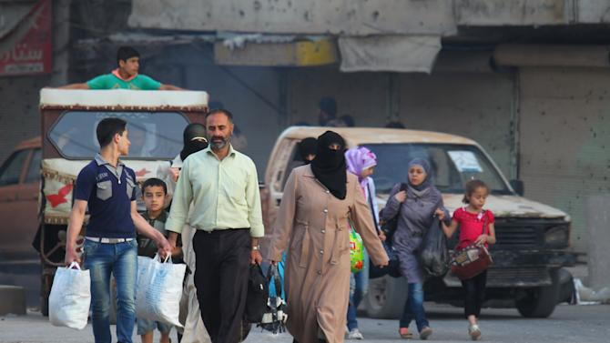 Residents carry their belongings as they flee the northwestern city of Ariha, after a coalition of insurgent groups seized the area in Idlib province