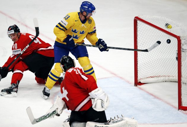 Sweden's Sedin scores the puck past Switzerland's Josi and Gerber during their 2013 IIHF Ice Hockey World Championship final match at the Globe Arena in Stockholm