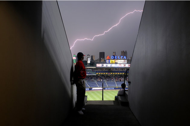 Usher Brent Mole stands along a wall as lightning strikes across the sky during a storm delay for the MLB National League baseball game between the Atlanta Braves and New York Mets at Turner Field in