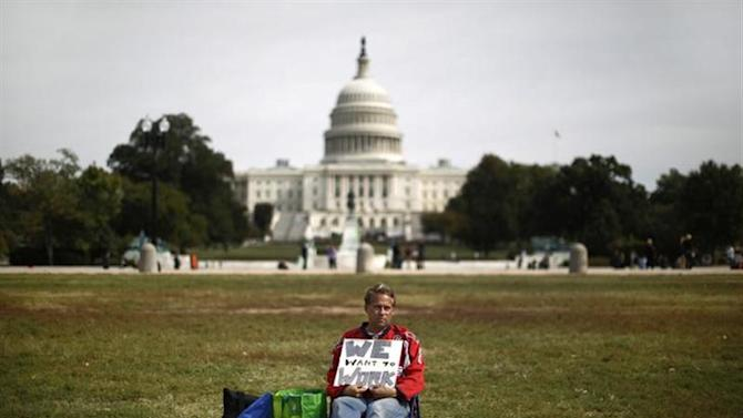 Furloughed Americorps employee Jeffrey Wismer sits alone on the Washington Mall October 8, 2013, as he calls on congress to end the government shut down. REUTERS/Jason Reed