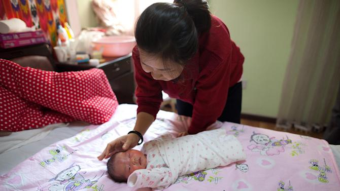 A mother tends to her newborn baby girl in Beijing on January 26, 2012