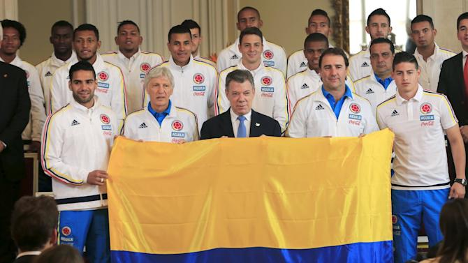 Santos poses after handing the national flag to national soccer team during a ceremony at presidential palace in Bogota
