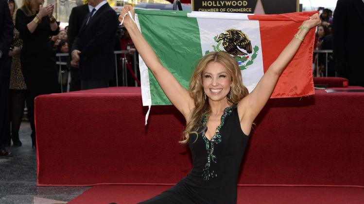 Performer Thalia holds up the Mexican flag as she poses on her star after it was unveiled on the Hollywood Walk of Fame in Hollywood