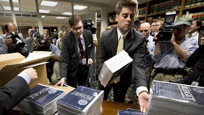 Copies of President Barack Obama's budget plan for fiscal year 2014 are distributed to Senate staff on Capitol Hill in Washington, Wednesday, April 10, 2013. The president sent Congress a $3.77 trillion spending blueprint that seeks to tame runaway deficits by raising taxes further on the wealthy and trimming popular benefit programs but has drawn angry responses from both the right and left. (AP Photo/J. Scott Applewhite)