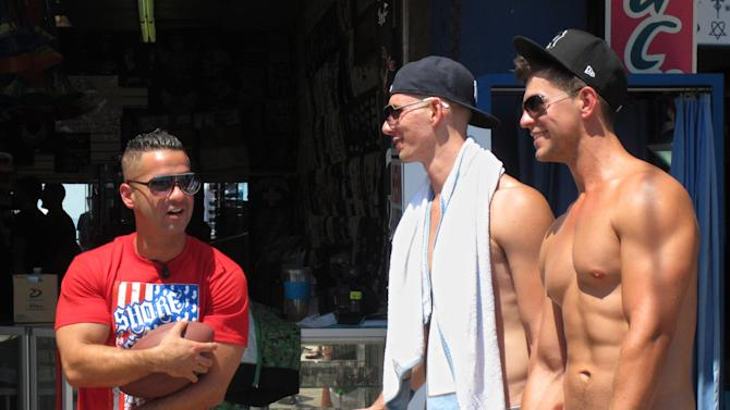 """Michael """"The Situation"""" Sorrentino speaks with Rafael Kieliszelic, center, and Daniel Sajewski, both of Toronto, Canada, on the boardwalk in Seaside Heights, N.J., during a break in taping of an episode of the MTV series """"Jersey Shore,"""" Friday, July 15, 2011. A new nationwide poll finds the show's depiction of a group of hard-drinking, foul-mouthed 20-somethings has not hurt New Jersey's national image, and may help it in some small ways. (AP Photo/Wayne Parry)"""