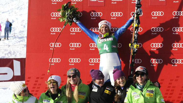 Alice McKennis, from the United States, top, celebrates with her teammates after wining an alpine ski, women's World Cup downhill in St. Anton, Austria, Saturday, Jan.12, 2013. (AP Photo/Giovanni Auletta)