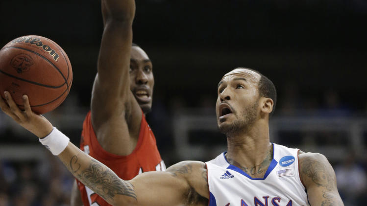 Kansas guard Travis Releford (24) drives past Western Kentucky forward O'Karo Akamune (15) during the first half of a second-round game in the NCAA men's college basketball tournament in Kansas City, Mo., Friday, March 22, 2013. (AP Photo/Orlin Wagner)