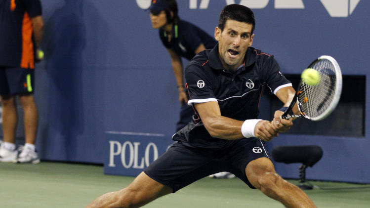 Novak Djokovic, of Serbia, returns to Nikolay Davydenko, of Russia, during the third round of the U.S. Open tennis tournament in New York, Saturday, Sept. 3, 2011. (AP Photo/Elise Amendola)