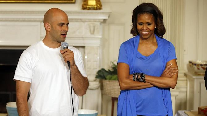 "FILE - In this June 12, 2104, file photo, first lady Michelle Obama stands with Sam Kass, White House Senior Policy Adviser for Nutrition Policy, before they make salads from vegetables harvested from the White House garden with area students in the State Dining Room of the White House in Washington. President Barack Obama's personal chef is leaving after nearly six years in which, unlike any assistant White House chef before him, he cooked up policy alongside his meals. Kass held the title of senior policy adviser for nutrition policy, which gave him a seat at the table to help administration officials hash out everything from an updated ""Nutrition Facts"" label for processed foods to new government standards to cut the amount of fat, calories and sodium in federally subsidized school meals. (AP Photo/Charles Dharapak, File)"