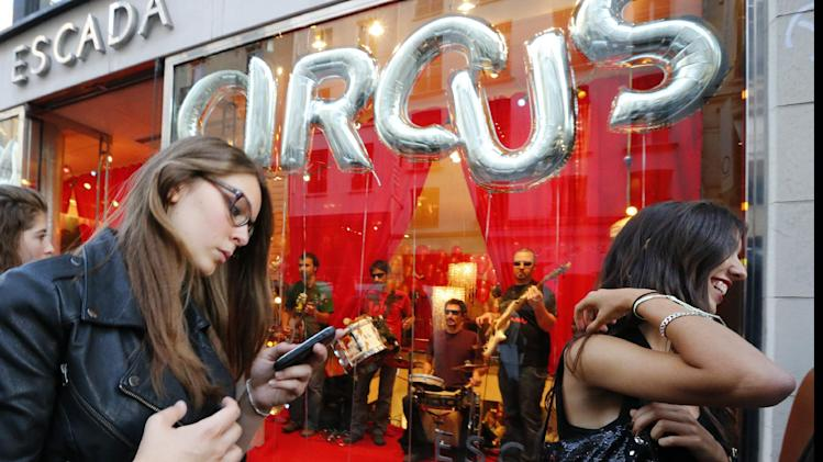 Parisians walk past fashion shops  in the streets of Paris, Thursday Sept. 6 2012, during Fashion's Night Out where fashion shops open  their doors at night  to encourage consumers to support the fashion industry.(AP Photo/Jacques Brinon)