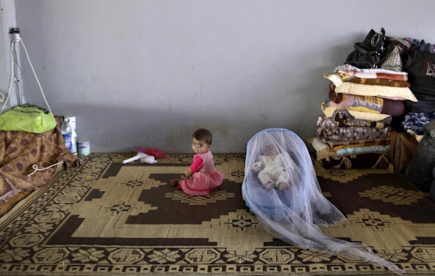 Syrian child, Taybah Al-Hajji, 1, whose family fled their home in Aleppo 15 days ago due to Syrian government shelling, sits next to her one month old brother Abdulghani, sleeping in a child safety seat covered with a mosquito net, as they take refuge with their family at the Bab Al-Salameh border crossing, in hopes of entering one of the refugee camps in Turkey, near the Syrian town of Azaz, Thursday, Sept. 6, 2012. (AP Photo/Muhammed Muheisen)