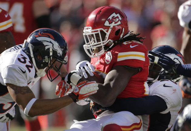 Kansas City Chiefs running back Jamaal Charles (25) is tackled by Denver Broncos strong safety Mike Adams, right, and defensive back Tony Carter (32) during the first half of an NFL football game at A