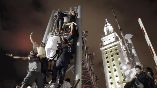 Miami Heat fans climb the sign stanchion outside American Airline Stadium while celebrating in Miami on Thursday June 20, 2013 after the Heat won the 2013 NBA Championship against the San Antonio Spurs. The Heat beat the San Antonio Spurs 95-88 in Game 7 of the NBA finals to win their second straight title. (AP Photo/Javier Galeano)