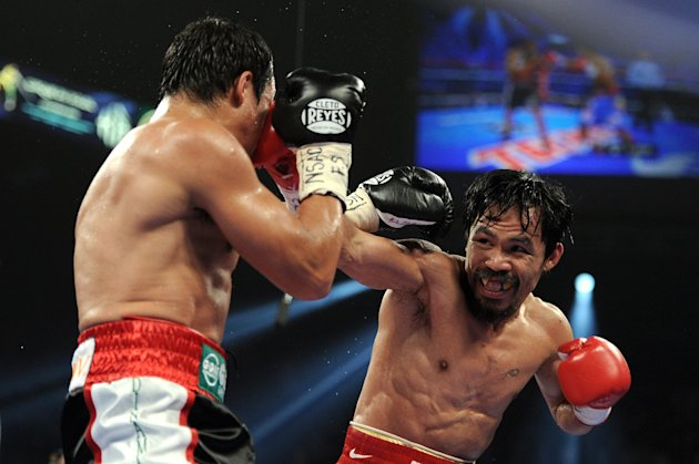 LAS VEGAS, NV - NOVEMBER 12:  (R-L) Manny Pacquiao throws a right to the head of Juan Manuel Marquez during the WBO world welterweight title fight at the MGM Grand Garden Arena on November 12, 2011 in Las Vegas, Nevada.  (Photo by Harry How/Getty Images)