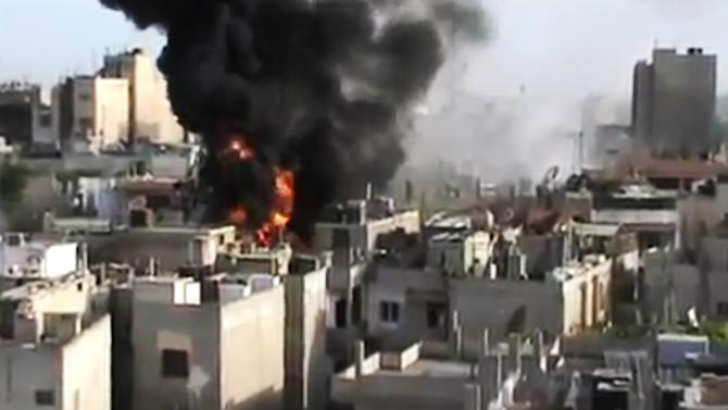 In this image made from amateur video released by the Shaam News Network and accessed Wednesday, May 23, 2012, purports to show a building on fire from shelling in Homs province, Syria. A United Nations team in Syria says it has brokered an exchange between forces loyal to President Bashar Assad and opposition fighters seeking to topple his regime. (AP Photo/Shaam News Network via AP video) TV OUT, THE ASSOCIATED PRESS CANNOT INDEPENDENTLY VERIFY THE CONTENT, DATE, LOCATION OR AUTHENTICITY OF THIS MATERIAL