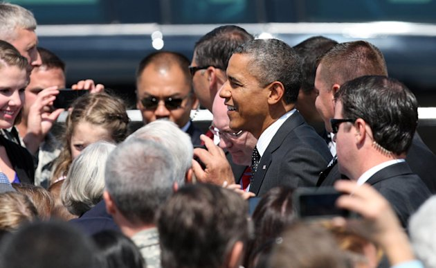 President Barack Obama greets supporters upon his arrival, Tuesday, July 24, 2012, at the 142nd Fighter Wing Oregon Air National Guard Base, in Portland, Ore. President Barack Obama has arrived in Oregon to raise money for his re-election campaign. (AP Photo/Rick Bowmer)