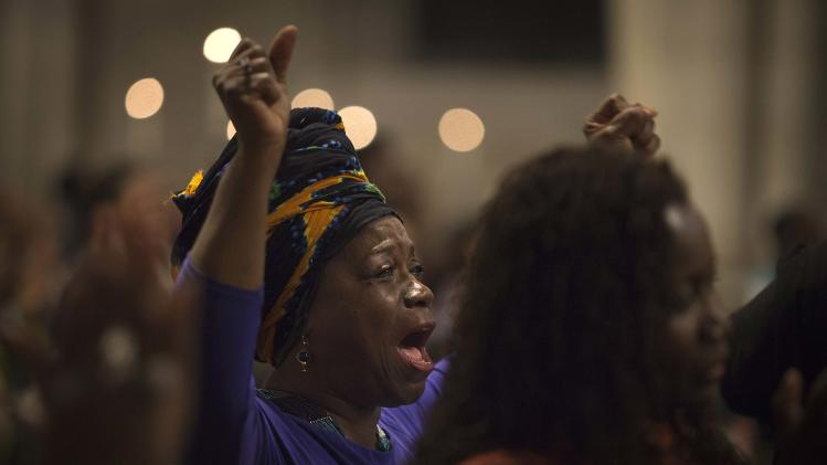 A woman raises her arms in song during a memorial service for the late Nelson Mandela at the Riverside Church in New York