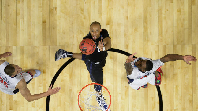 Xavier guard Myles Davis, center, shoots as Arizona center Kaleb Tarczewski, left, and forward Rondae Hollis-Jefferson defend during the second half of a college basketball regional semifinal in the NCAA Tournament, Thursday, March 26, 2015, in Los Angeles. (AP Photo/Mark J. Terrill)