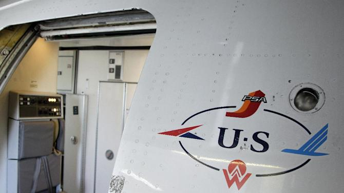 """In this Thursday, Sept. 27, 2012, photo, the US Airways 'Heritage"""" logo is shown by the door of a jet parked at the Charlotte/Douglas International airport in Charlotte, N.C. Patched together from several scrappy regional carriers on the brink of bankruptcy, US Airways has often been ridiculed within the aviation industry and remains a perennial afterthought among travelers. But it hopes to shed that image by merging with the larger American Airlines, in a deal which will catapult the two to the top of the industry. (AP Photo/Chuck Burton)"""