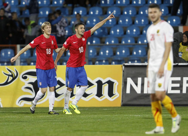 Serbia's Dusan Tadic, center and Dusan Basta celebrate his goal during their World Cup 2014 Group A qualifying soccer match against Macedonia, at the City Stadium in Jagodina, Serbia, Tuesday, Oct. 15