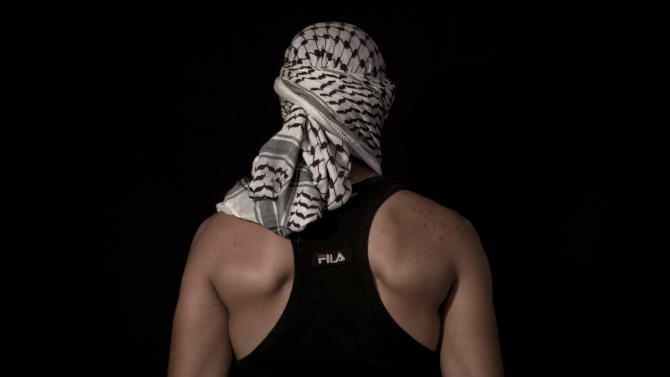 In this Monday, June 11, 2012 photo, a Palestinian stone thrower poses for a portrait in the West Bank village of Bilin, near Ramallah. The stone thrower is one of seven men who agreed to pose for a series of twelve portraits. (AP Photo/Oded Balilty)