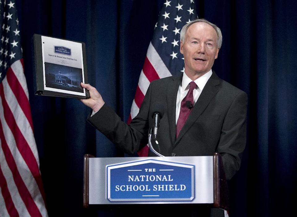 National School Shield Task Force Director, former Arkansas Rep. Asa Hutchinson, holds a copy of group's study during a news conference at National Press Club in Washington, Tuesday, April 2, 2013. The National Rifle Association's study recommends schools across the nation each train and arm at least one staff member.  (AP Photo/Jose Luis Magana)