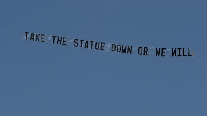"""A plane flying the Penn State University campus in State College, pulls a banner reading """"Take the statue down or we will"""" on Tuesday, July 17, 2012. The Paterno statue outside Beaver Stadium has been a point of much contention. Critics have called for the statue to be taken down after the Freeh report concluded that Paterno was aware of a 1998 allegations against Sandusky _ in contrast to his grand jury testimony and an interview given after his firing _ and that he was involved in the decision to not report a 2001 incident to the authorities even after his superiors had decided to. (AP Photo/Centre Daily Times, Nabil K. Mark) MAGS OUT, MANDATORY CREDIT"""