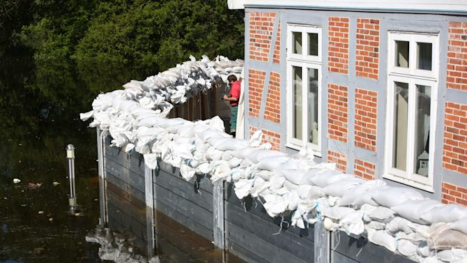 A helper controls a wall erected to protect a restaurant from Elbe floodwater in Lauenburg, northern Germany, Monday June 10, 2013. Weeks of heavy rain this spring have sent the Elbe, the Danube and other rivers such as the Vltava and the Saale overflowing their banks, causing extensive damage in central and southern Germany, the Czech Republic, Austria, Slovakia and Hungary. (AP Photo/dpa,Christian Charisius)