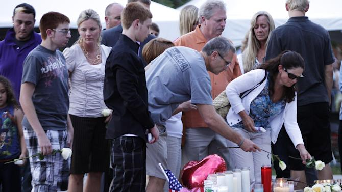 """Family members of the victims of Friday's mass shooting in Aurora, Colo., leave roses at a memorial as they leave a prayer vigil, Sunday, July 22, 2012, in Aurora, Colo. 12 people were killed and 58 were injured in a shooting during an early Friday premiere of """"The Dark Knight Rises."""" (AP Photo/Ted S. Warren)"""
