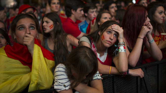 Spanish soccer fans gesture as they watch on a giant display the World Cup soccer match between Spain and Chile, in Madrid, Spain, Wednesday, June 18, 2014. (AP Photo/Andres Kudacki)