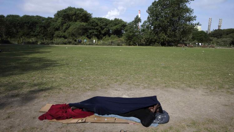 "An African migrant sleeps on the grass in the ""jungle"" close to a chemical factory in Calais"