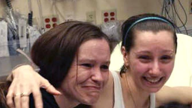 FILE - In this Monday, May 6, 2013 file photo, Amanda Berry, right, hugs her sister Beth Serrano after being reunited in a Cleveland hospital. For Berry, Gina DeJesus and Michelle Knight, who were freed from captivity inside a Cleveland house on Monday, the ordeal is not over. Next comes recovery _ from sexual abuse and their sudden, jarring reentry into a world much different than the one they were snatched from a decade ago. (AP Photo/Family Handout courtesy WOIO-TV, File)