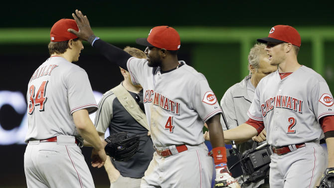Cincinnati Reds starting pitcher Homer Bailey (34) is congratulated by second baseman Brandon Phillips (4) and shortstop Zack Cozart (2) after the Reds defeated the Miami Marlins 6-2 in a baseball game in Miami, Tuesday, May 14, 2013. (AP Photo/Lynne Sladky)