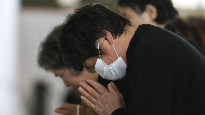 People offer prayers during a memorial service honoring victims of the March 11, 2011 earthquake and tsunami, a day before the second anniversary of the disaster in Rikuzentakata, Iwate Prefecture, northern Japan Sunday, March 10, 2013. Over 15,000 people were killed in the disaster. (AP Photo/Shizuo Kambayashi)