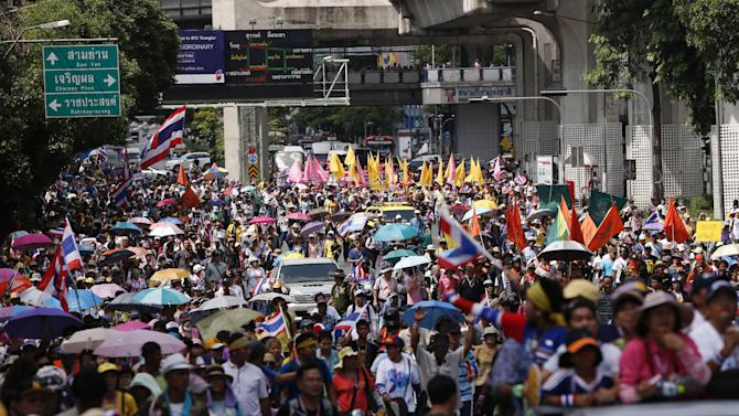 Anti-government protesters march through a main road in downtown Bangkok, Thailand, Friday, May 9, 2014. Thailand's anti-graft commission indicted ousted Prime Minister Yingluck Shinawatra on Thursday on charges of dereliction of duty in overseeing a widely criticized rice subsidy program, a day after a court forced her from office. Yingluck was accused of allowing the rice program, a flagship policy of her administration, to proceed despite advice that it was potentially wasteful and prone to corruption. (AP Photo/Vincent Thian)