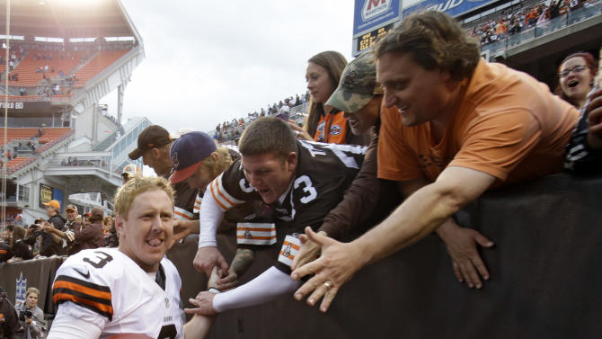 Cleveland Browns quarterback Brandon Weeden celebrates with fans after the Browns defeated the Cincinnati Bengals 34-24 in an NFL football game Sunday, Oct. 14, 2012, in Cleveland. Weeden got his first NFL win on his 29th birthday. (AP Photo/Mark Duncan)