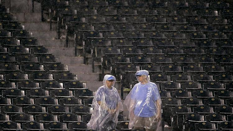 Fans watch from the stands during a rain delay in the sixth inning of a baseball game between the Kansas City Royals and the Cleveland Indians Friday, Aug. 29, 2014, in Kansas City, Mo. (AP Photo/Charlie Riedel)