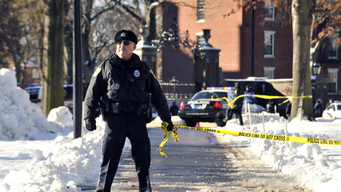 A police officer holds tape to keep people out from an area at Harvard University in Cambridge, Mass., Monday, Dec. 16, 2013. Four buildings on campus were evacuated after campus police received an unconfirmed report that explosives may have been placed inside, interrupting final exams. (AP Photo/Josh Reynolds)