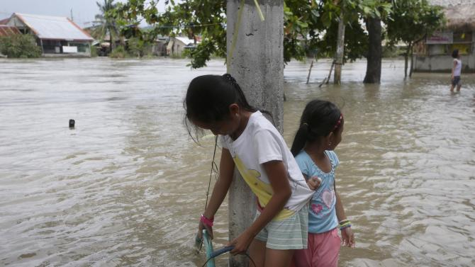 Residents fetch potable water amidst flooding brought about by monsoon rains that was induced by Typhoon Halong, Tuesday, Aug. 5, 2014 at Hermosa township, Bataan province in northwestern Philippines. It was the 10th weather disturbance in the country this year which averages about 20 typhoons a year. (AP Photo/Bullit Marquez)