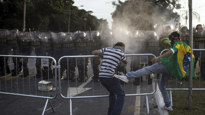 A protester kicks another one as he tries to prevent him from breaking a police barrier during a protest outside Minerao stadium where a Confederations Cup soccer match takes place between Japan and Mexico in Belo Horizonte, Brazil, Saturday, June 22, 2013. Demonstrators once again took to the streets of Brazil on Saturday, continuing a wave of protests that have shaken the nation and pushed the government to promise a crackdown on corruption and greater spending on social services. (AP Photo/Felipe Dana)