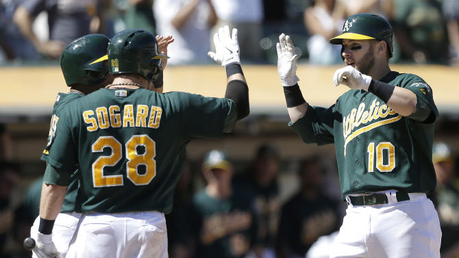 Oakland Athletics' Daric Barton (10) is congratulated by teammates Alberto Callaspo, left, and Eric Sogard (28) after hitting a two-run home run off Texas Rangers pitcher Yu Darvish, from Japan, during the sixth inning of a baseball game in Oakland, Calif., Wednesday, Sept. 4, 2013. (AP Photo/Jeff Chiu)